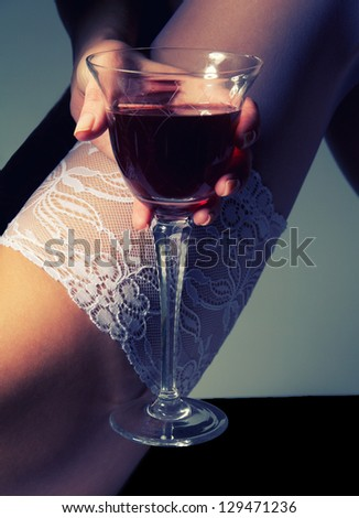 woman feet in white stockings with wineglass on gray background