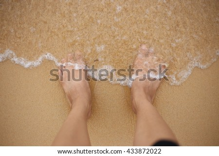 woman feet on a tropical sandy beach - stock photo