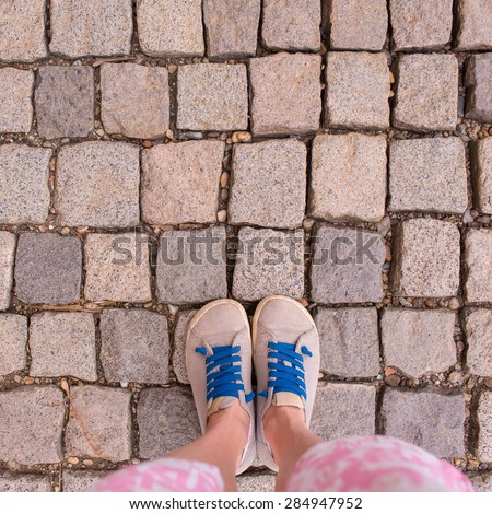 Woman feet on the old stone road - stock photo