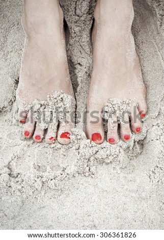 woman feet on the sand in the beach, red polished nails - stock photo