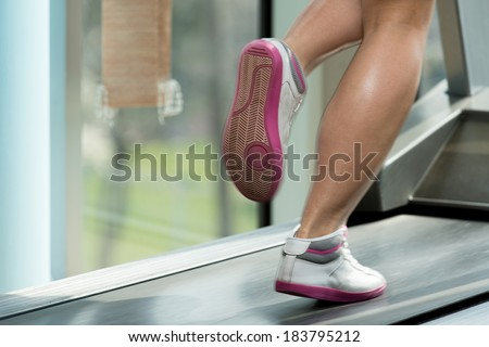 Woman Feet On Treadmill - Close-Up Of Female Legs Running On Treadmill - Blurred Motion - stock photo