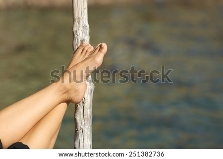 Woman feet relaxing on holidays in a beach or lake with the sea water in the background - stock photo