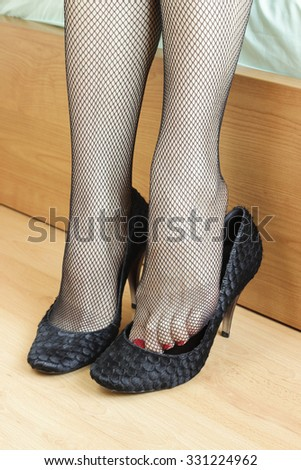 Woman feet with fishnet tights and heels - stock photo