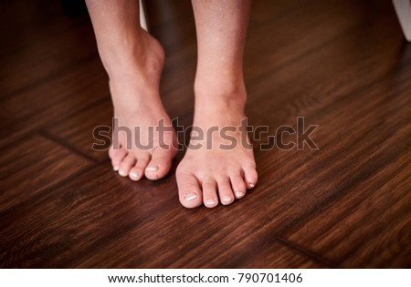 Woman feet with pedicure on wooden floor