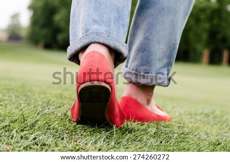 Woman feet with red fashion shoes and jeans in a spring park