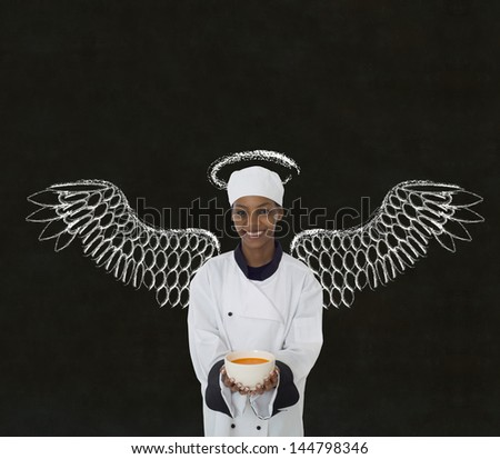 Woman female African or African American chef holding food soup bowl with angels wings and halo chalk blackboard background - stock photo
