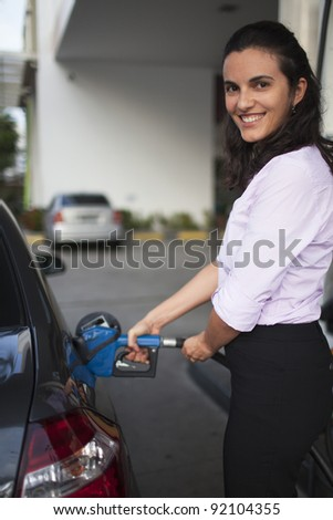 Woman fill up car - stock photo