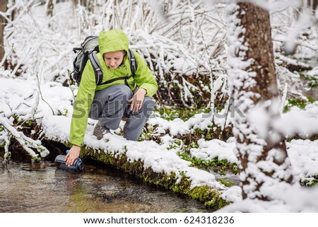 woman filling bottle of water from a winter forest stream. travel and vacation concept