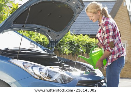 Woman Filling Car Radiator With Water