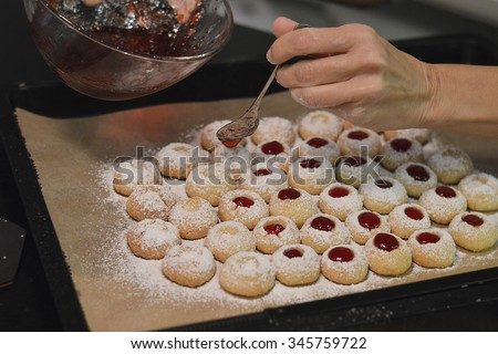 Woman filling jam into Christmas cookies - stock photo
