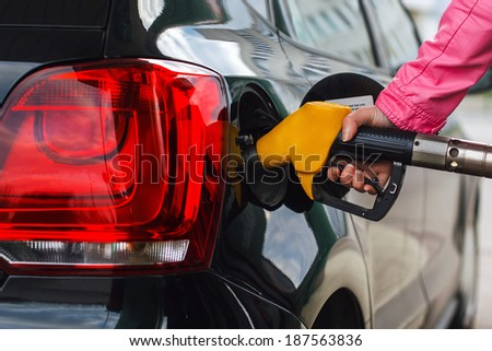 Woman filling up car at petrol station - stock photo