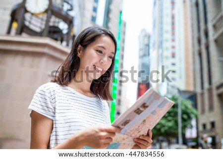 Woman finding the location on city map in Hong Kong - stock photo
