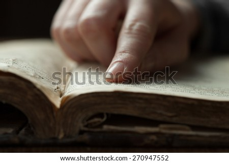 woman finger presses on old bible book in a dark romm over wooden table and reading