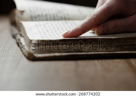 woman finger presses on old bible book in a dark room over wooden table and reading a bible - stock photo