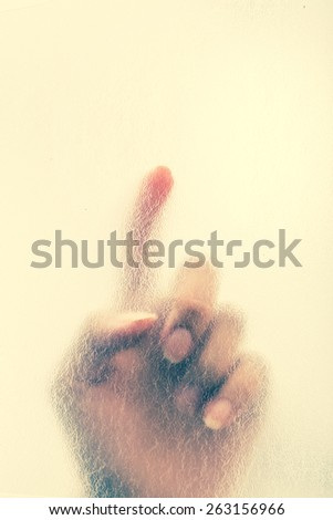 Woman finger touch on transparent film. Vintage filter - stock photo