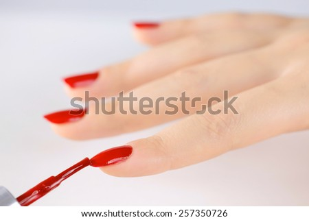 woman fingernails with red nail polish
