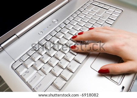 Woman fingers on laptop keyboard.
