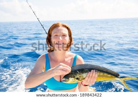 Woman fishing Dorado Mahi-mahi fish happy with trolling catch on boat deck - stock photo