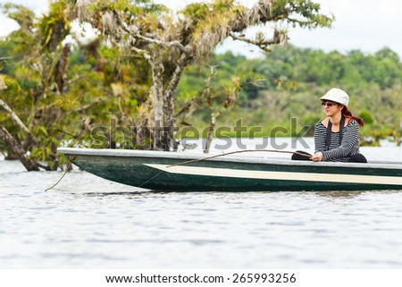 WOMAN FISHING PIRANHA IN CUYABENO NATIONAL PARK, ECUADOR  - stock photo