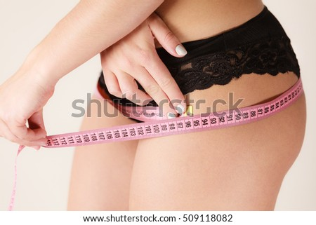 Woman fit girl in black lingerie measuring her hips with measure tape closeup. Part of female body.