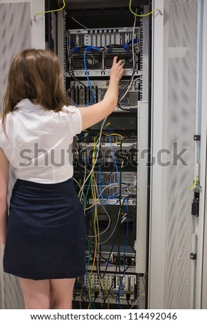 Woman fixing server wires in data center - stock photo