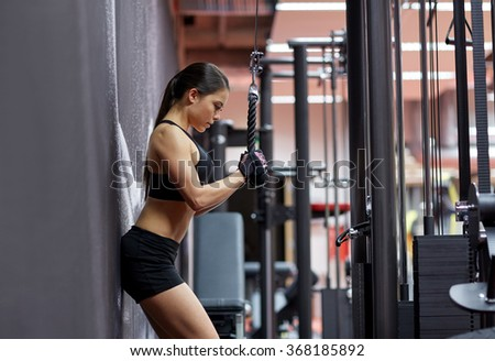 woman flexing arm muscles on cable machine in gym - stock photo