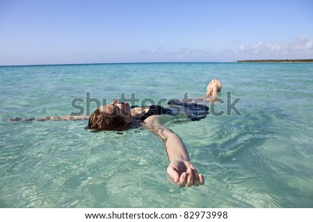 Woman floating and relaxing in the sea - stock photo