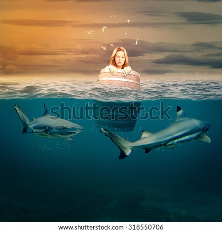 woman floating in a barrel surrounded by sharks - stock photo