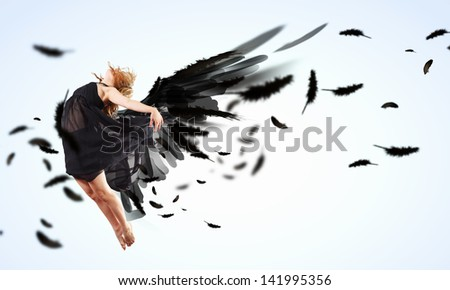 Woman floating in a dance on dark wings. Collage.