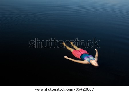 Woman Floating in Dark Blue Lake - stock photo