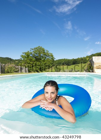 Woman floating in inner tube in pool and smiling at the camera. Vertical - stock photo