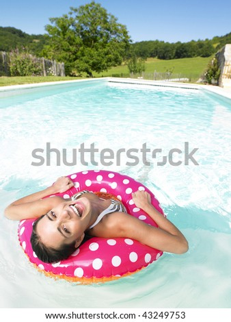 Woman floating in pink polka dot inner tube and laughing. Vertical. - stock photo