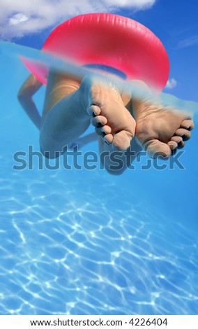 Woman floating in rubber ring in blue swimming pool - stock photo