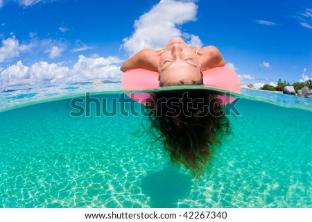 woman floating on tropical pink inflatable inner tube in tropical water in virgin islands, caribbean