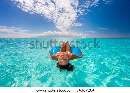 woman floats on blue inner tube in turquoise waters in tahiti with bikini on beautiful summer vacation - stock photo