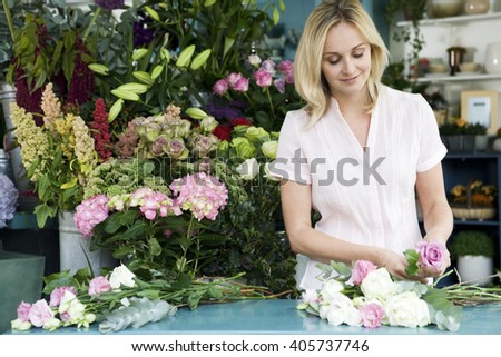 Woman florist creating a bouquet of pink and white roses - stock photo