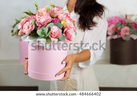 Woman florist making a lovely flower composition in a flower shop