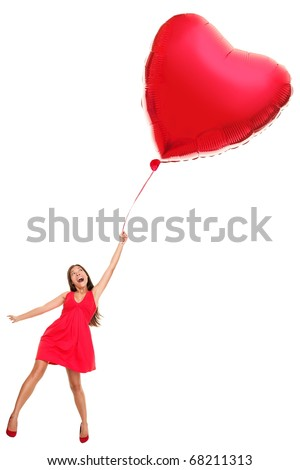 Woman flying away with red heart balloon. Funny valentines day love concept image of beautiful cute young woman in red dress. Asian / Caucasian girl isolated on white background in full length. - stock photo