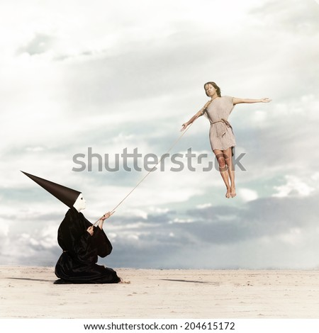 Woman flying like a kite driven by the mysterious person dressed in the black cloak - stock photo