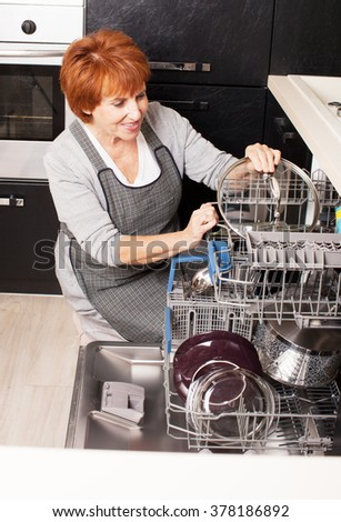 Woman folding the dishes in the dishwasher. Female at kitchen. Housework