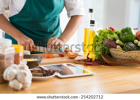 Woman following recipe on digital tablet and cooking healthy meal - stock photo