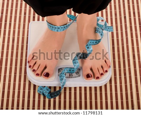 Woman foot on measuring tape. - stock photo