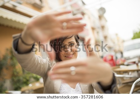 Woman framing with hands and looking at the view.