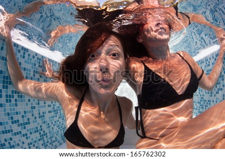 Woman friends having fun underwater in swimming pool.  - stock photo