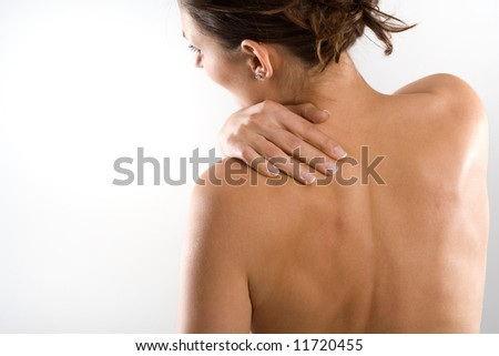 Woman from behind, naked body, holding her neck on the left side. Face to the left. - stock photo