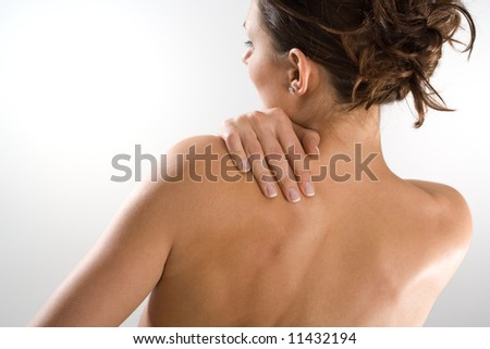 Woman from behind, naked body, holding her neck on the left side. Face to the left. Body tilt.