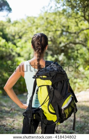 Woman front the back posing with her backpack on the wood - stock photo