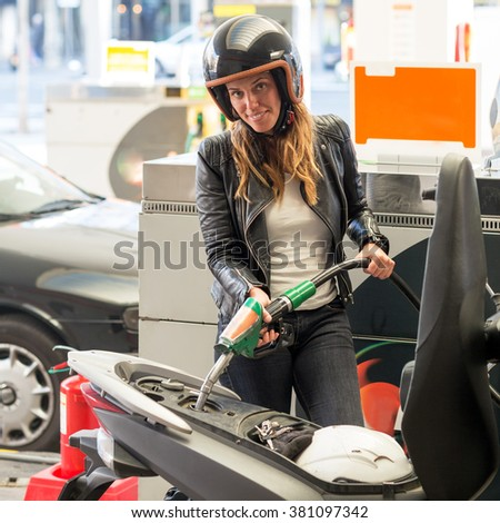 Woman fueling scooter at the gas station - stock photo