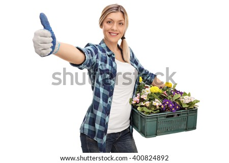 Woman gardener holding a rack of flowers and giving thumbs up isolated on white background