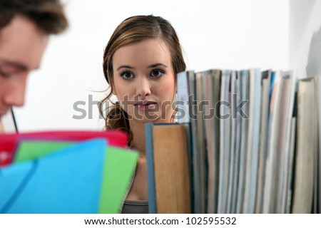 Woman gazing at a man in a library - stock photo